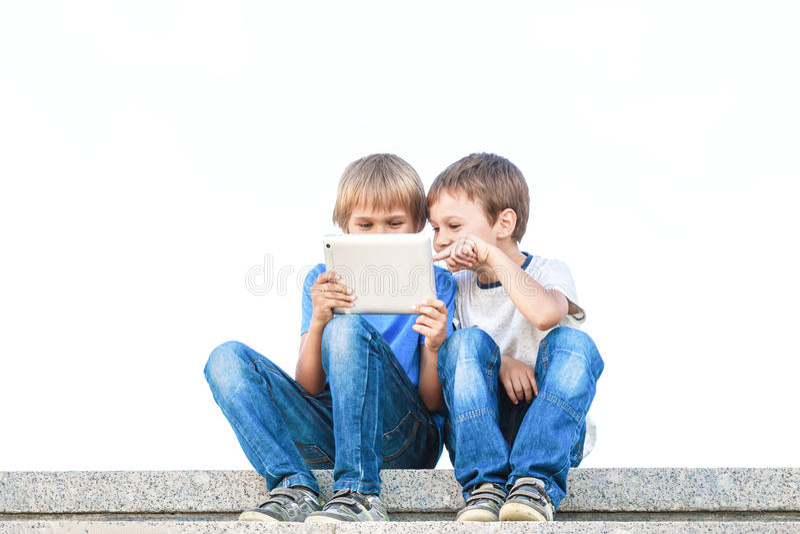 Dois meninos que olham o PC da tabuleta Infância, educação, aprendendo, tecnologia, conceito do lazer fotos de stock