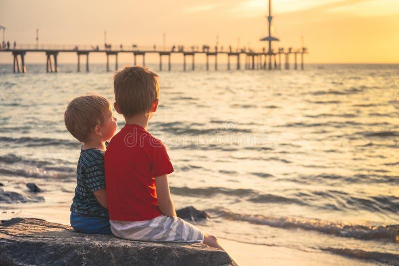 Dois meninos que sentam-se na rocha na praia no por do sol fotos de stock