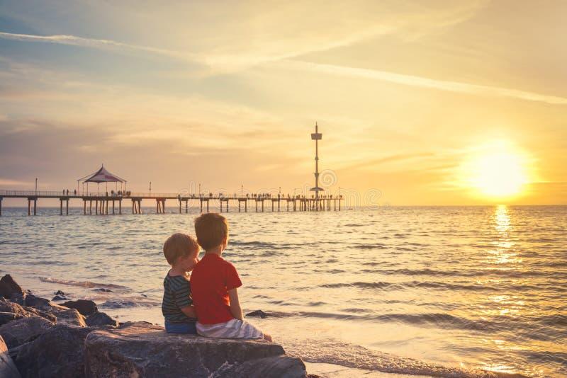 Dois meninos que sentam-se na rocha na praia no por do sol imagem de stock royalty free