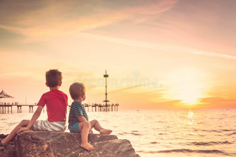 Dois meninos que sentam-se na rocha na praia no por do sol foto de stock