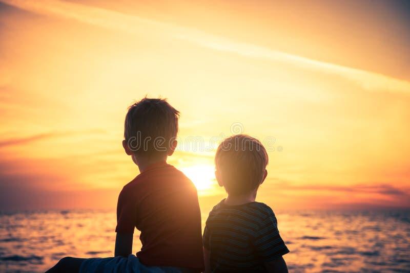 Dois meninos que sentam-se na rocha na praia no por do sol imagens de stock royalty free