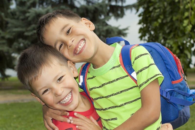 Dois meninos são irmãos nos braços foto de stock