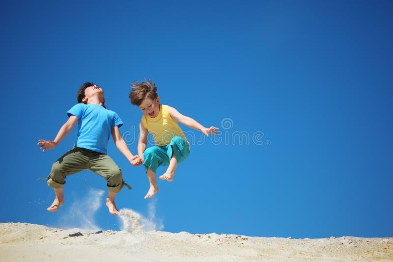 Dois meninos saltam na areia imagens de stock
