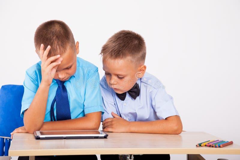 Dois meninos sentam-se em uma mesa e em uma tabuleta da vista imagem de stock