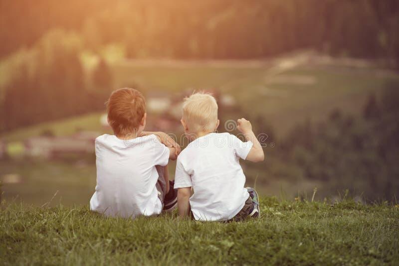 Dois meninos sentam-se no monte e na fala alegremente Vista traseira imagem de stock royalty free