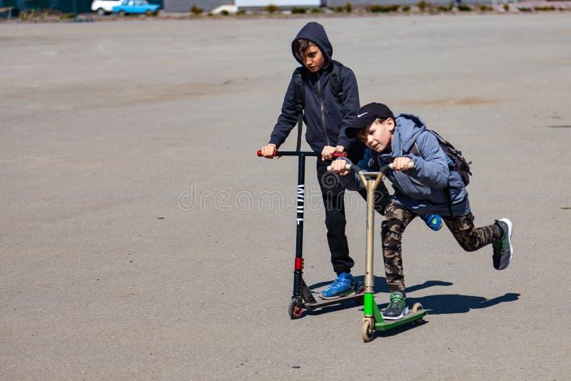 Dois meninos, um em um tampão, o outro em uma capa, rolo nos 'trotinette's que empurram fora de uma estrada com sorrisos em sua c foto de stock