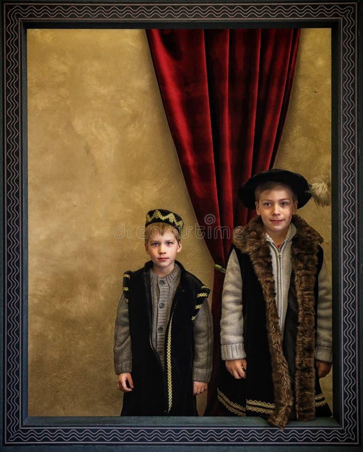Dois meninos vestidos como senhores medievais no quadro de madeira fotografia de stock royalty free