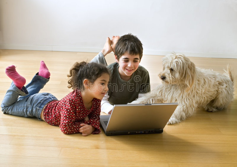 Dois miúdos com computador portátil e um cão