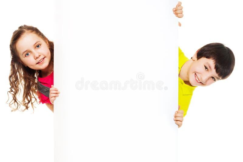 Dois miúdos com placa vazia do anúncio foto de stock