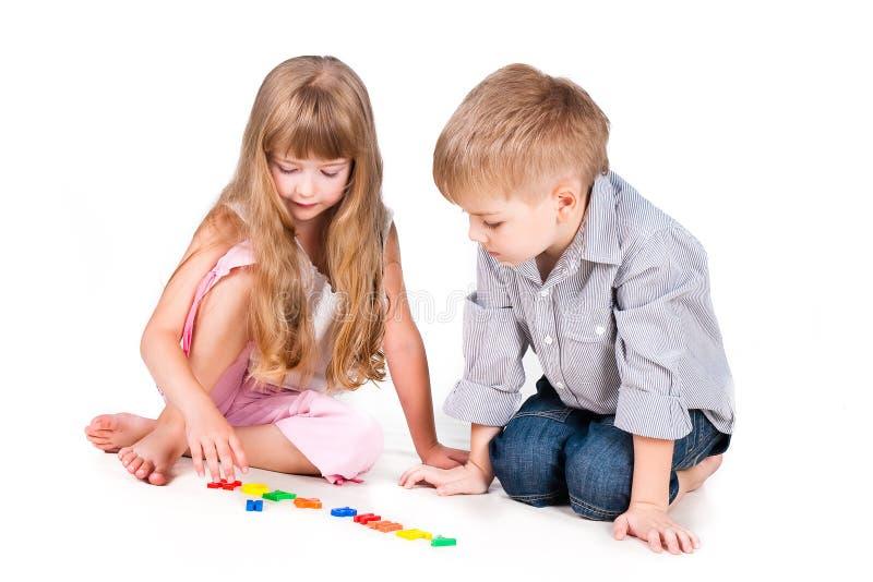 Dois miúdos de jogo com o alfabeto isolado no branco imagens de stock