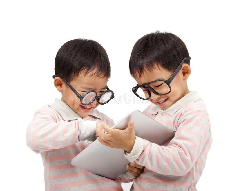 Dois miúdos felizes que usam o computador da almofada de toque