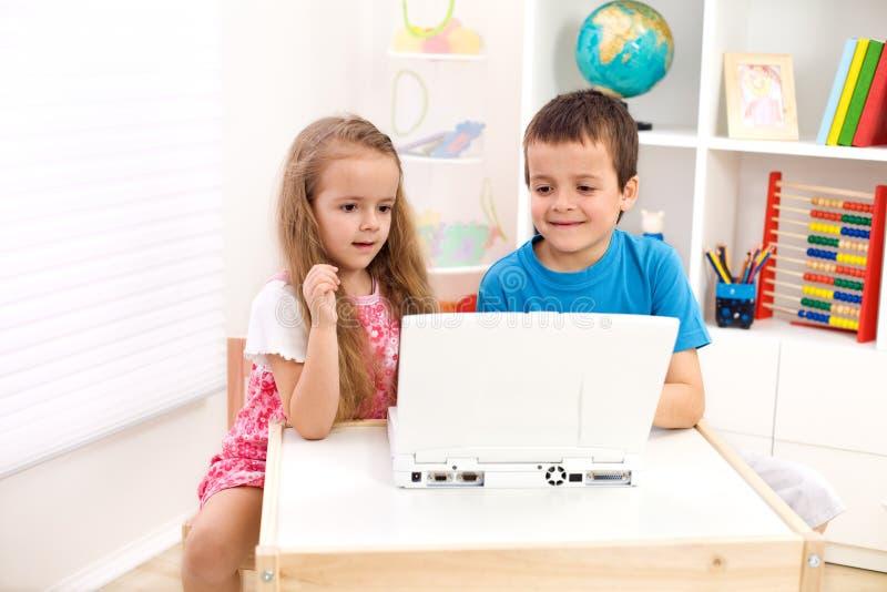 Dois miúdos que olham o computador portátil imagem de stock
