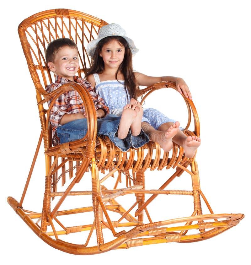 Dois miúdos que sentam-se na cadeira de balanço imagens de stock royalty free