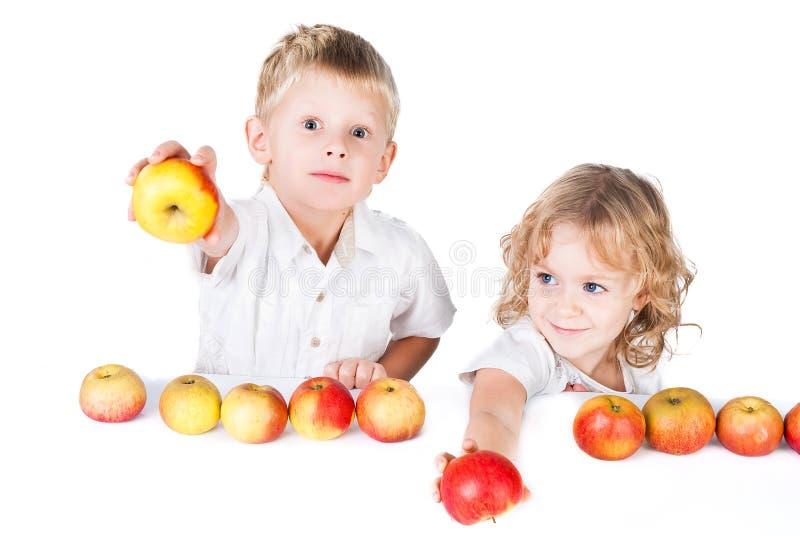 Dois miúdos submetem as maçãs isoladas no branco foto de stock royalty free