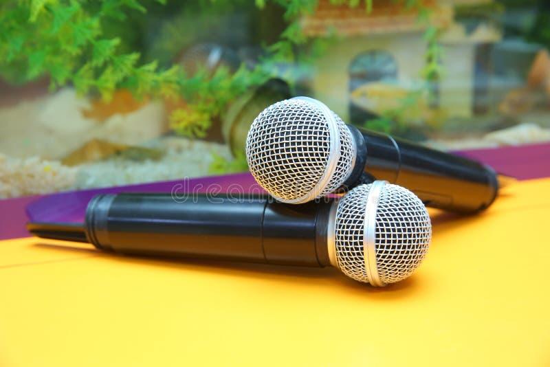 Dois microfones de prata isolados sobre o fundo amarelo Dois microfones sem fio na tabela de conferência fotos de stock royalty free
