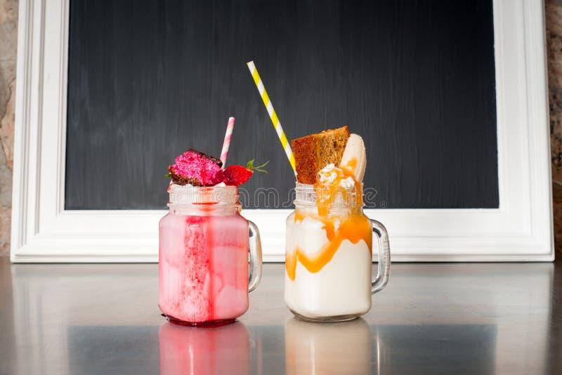 Dois milks shake loucos, com um quadro-negro vazio imagens de stock royalty free