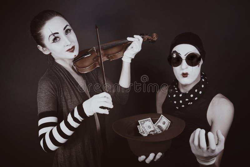 Dois mimicam jogando um violino para o dinheiro imagens de stock
