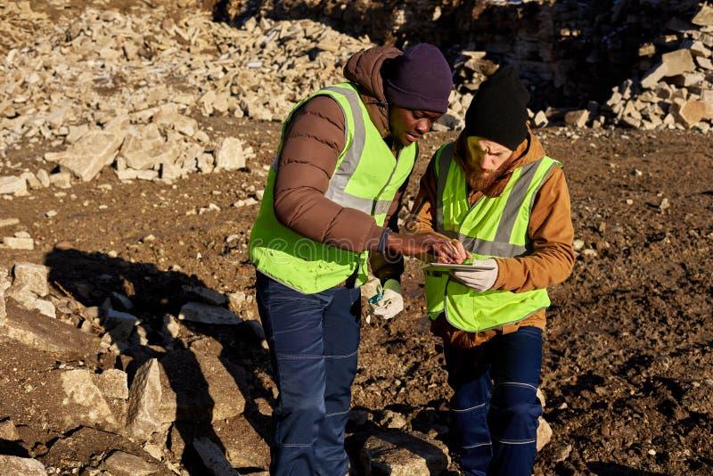 Dois mineiros de ouro que inspecionam a terra imagens de stock royalty free
