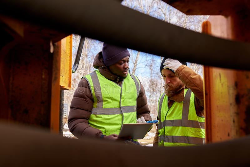 Dois mineiros que inspecionam o veículo imagem de stock royalty free