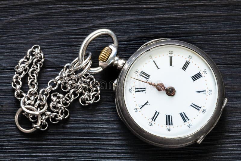 dois minutos a doze no relógio velho na madeira preta imagem de stock
