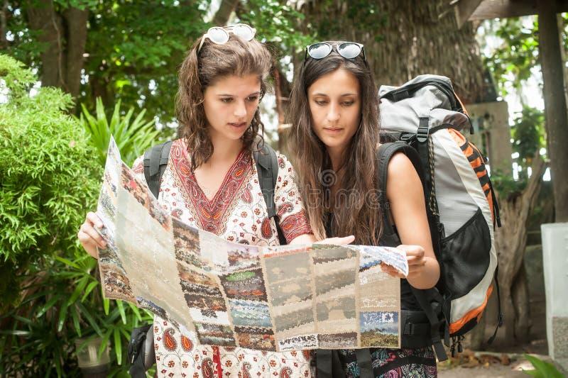 Dois mochileiros da mulher do viajante da aventura olham o mapa do turista imagem de stock