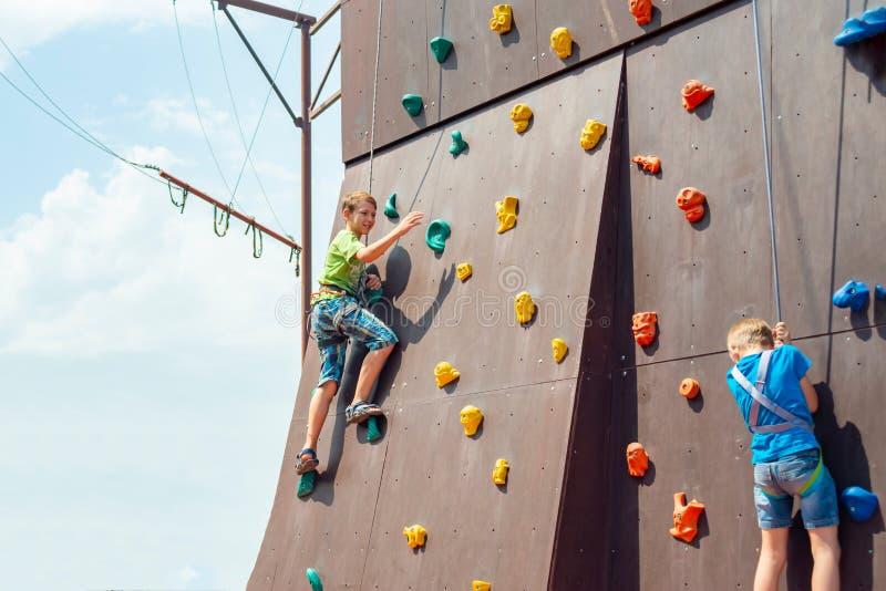 Dois montanhistas pequenos conquistam a cimeira de uma montanha artificial em um parque de diversões dos esportes fotografia de stock