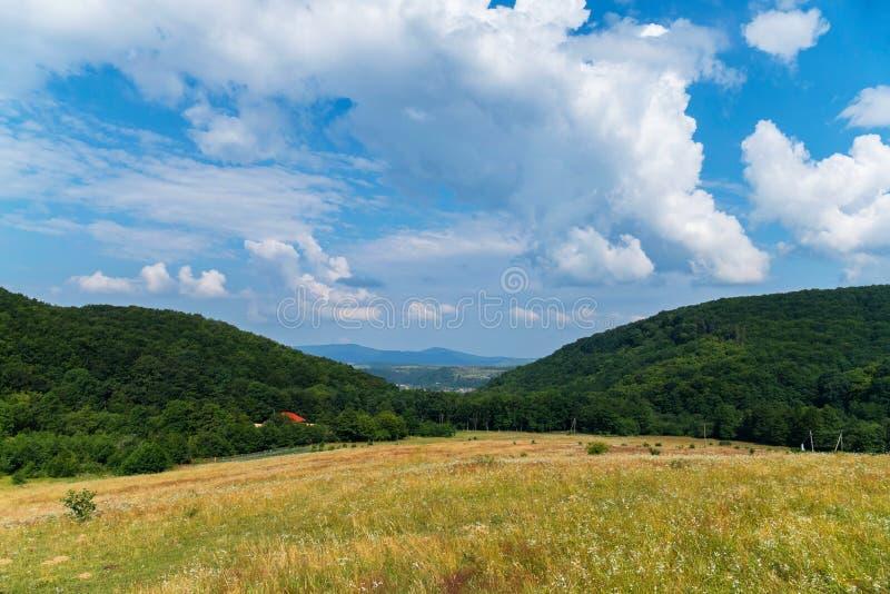 Dois montes paralelo-estando que abrem a vista do campo com grama seca a um grande vale com as montanhas na distância foto de stock
