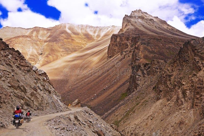 Dois motociclista em uma estrada da montanha do enrolamento no deserto da montanha da alta altitude nos Himalayas imagem de stock