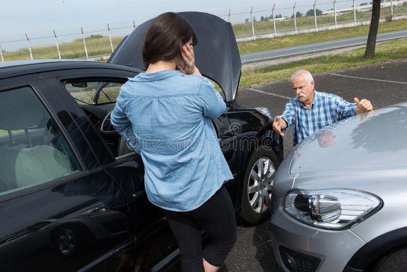 Dois motoristas que discutem após o acidente de tráfico fotografia de stock