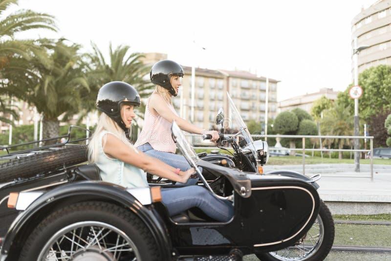 Dois mulheres louras da irmã feliz no side-car bike o sorriso e felizes imagem de stock
