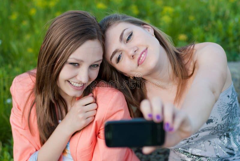 Dois mulheres novas & telefones felizes bonitos da foto foto de stock royalty free