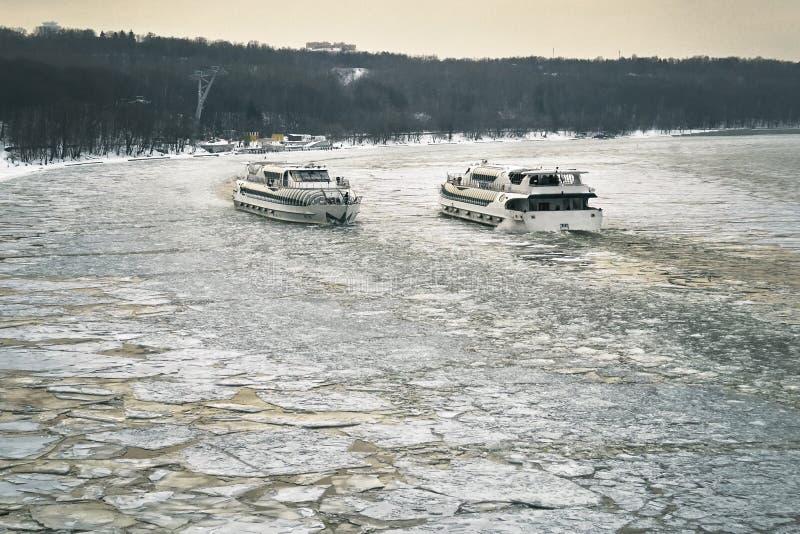 Dois navios que navegam ao longo do Moscou-rio coberto com um gelo quebrado para se foto de stock