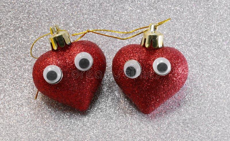 dois olhos em corações vermelhos sobre fundo prateado reluzente imagem de stock