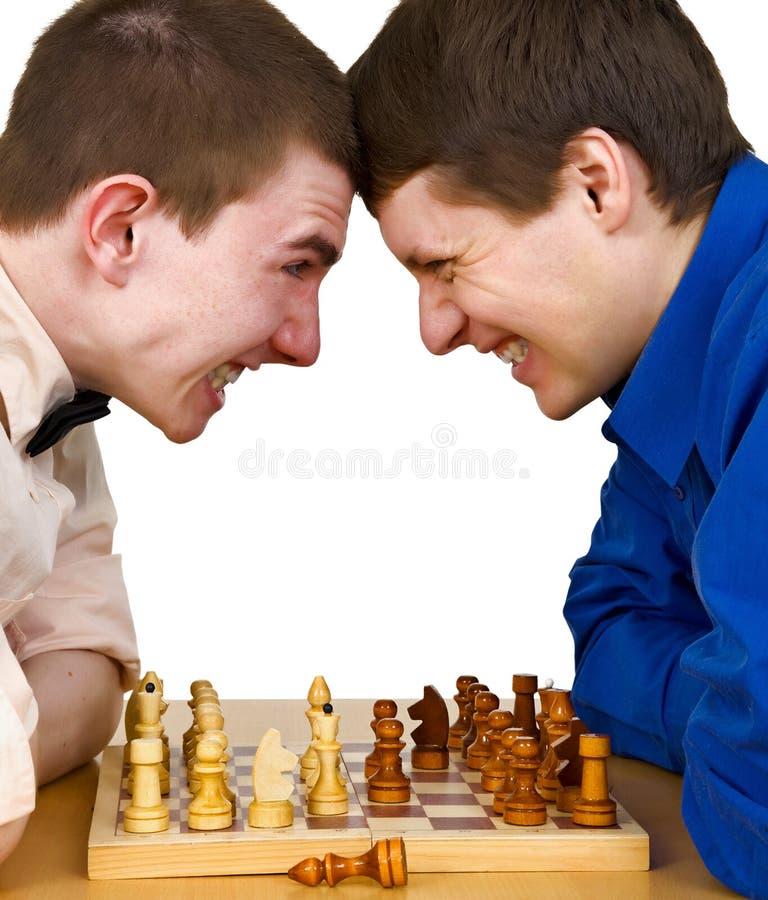 Dois oponentes agressivos da xadrez sob a placa de xadrez fotos de stock
