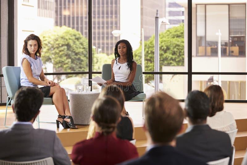 Dois oradores fêmeas sentam-se enfrentando a audiência no seminário do negócio fotos de stock