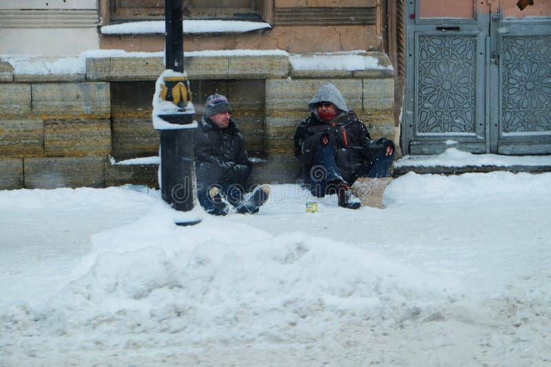 dois os sem-abrigo sentam-se em uma das ruas durante a queda de neve fotos de stock royalty free