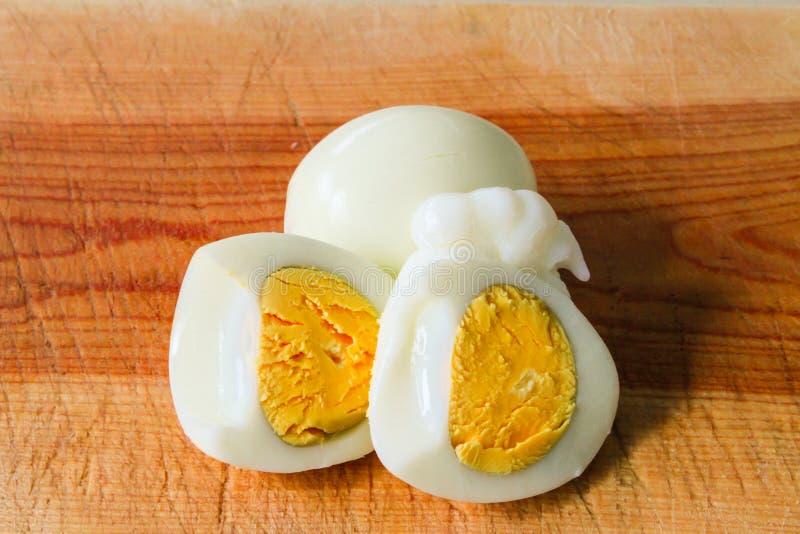 Dois ovos cozidos colocados em uma placa de corte de madeira imagens de stock royalty free