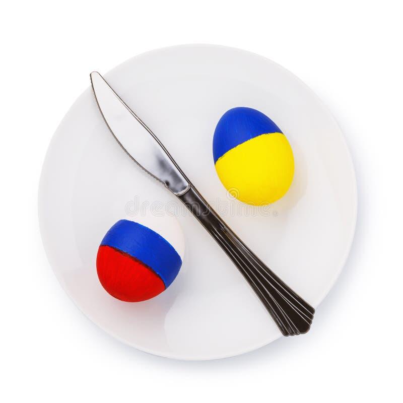Dois ovos da páscoa pintados na cor das bandeiras de Rússia e de Ucrânia em uma placa isolada em um fundo branco foto de stock royalty free