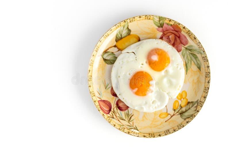 Dois ovos fritos na placa colorida isolada no fundo branco imagem de stock royalty free