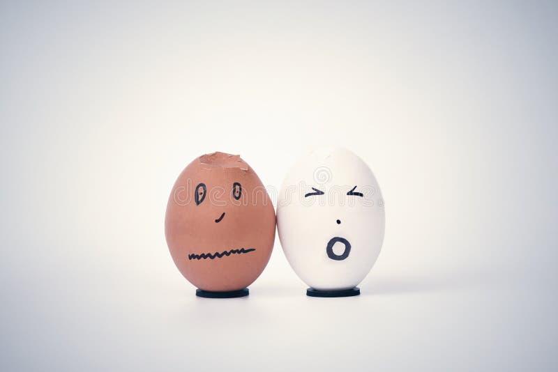 Dois ovos quebrados sob a forma da cabeça humana branca e preta em um suporte queixam-se entre si imagens de stock royalty free