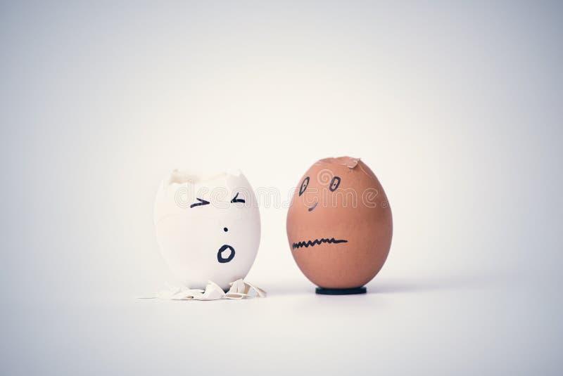 Dois ovos quebrados sob a forma da cabeça humana branca e preta em um suporte queixam-se entre si fotos de stock