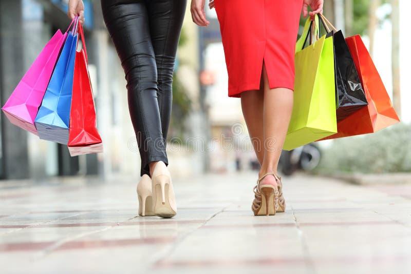 Dois pés das mulheres da forma que andam com sacos de compras foto de stock