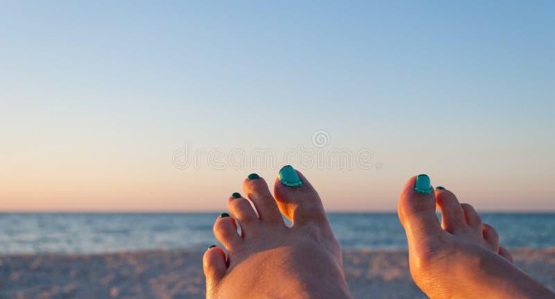 Dois pés fêmeas com os pregos pintados contra o contexto do mar e da areia fotos de stock