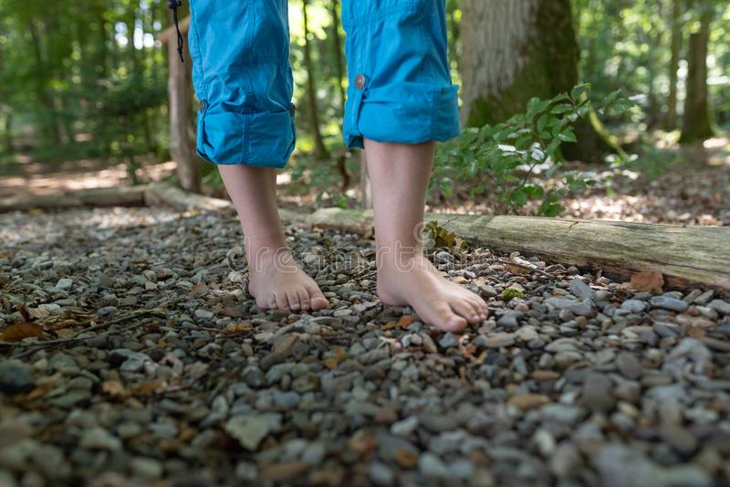 Dois pés fêmeas estão andando sobre seixos imagem de stock