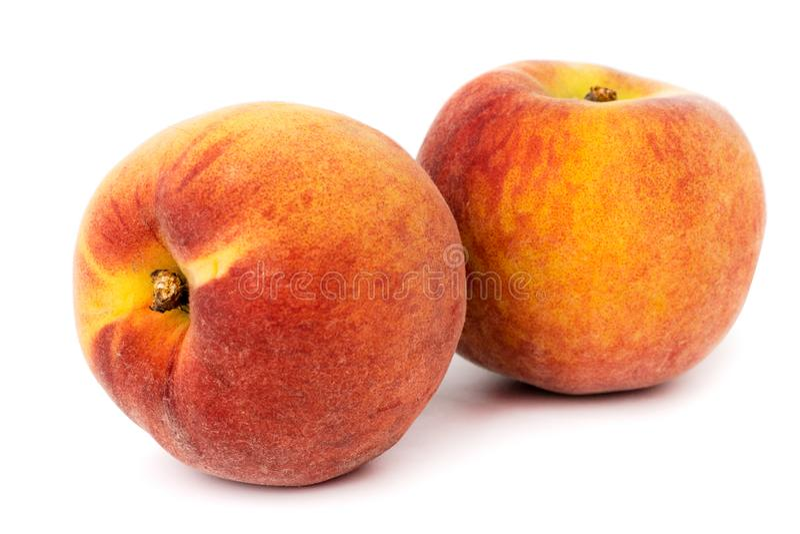 Dois pêssegos maduros em um fundo branco, fim acima imagens de stock