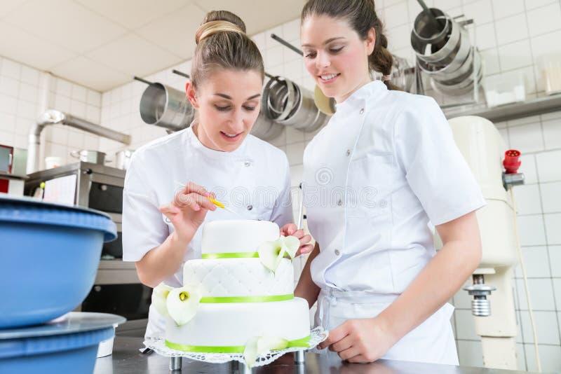 Dois padeiros da pastelaria que decoram o grande bolo fotos de stock royalty free