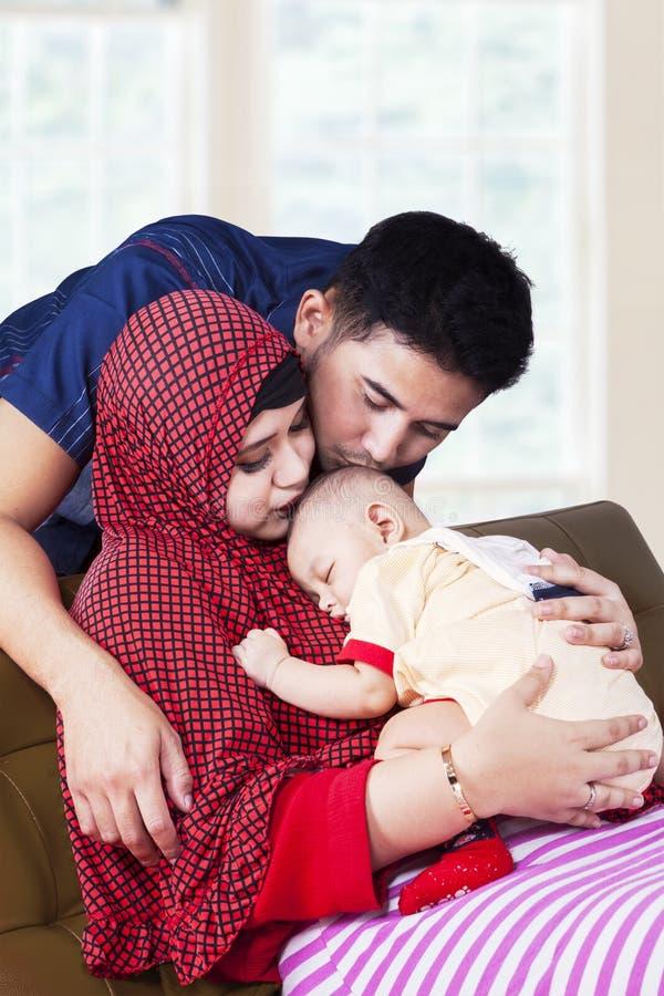 Dois pais muçulmanos beijam seu bebê imagens de stock royalty free