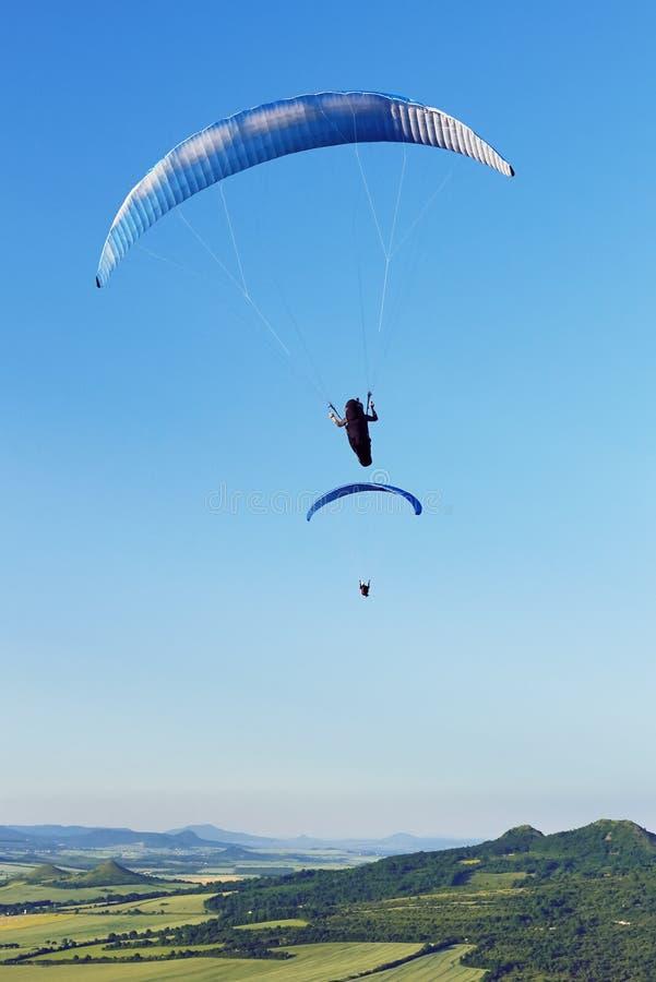 Dois Paragliders que voam sobre montanhas no dia de verão imagens de stock royalty free