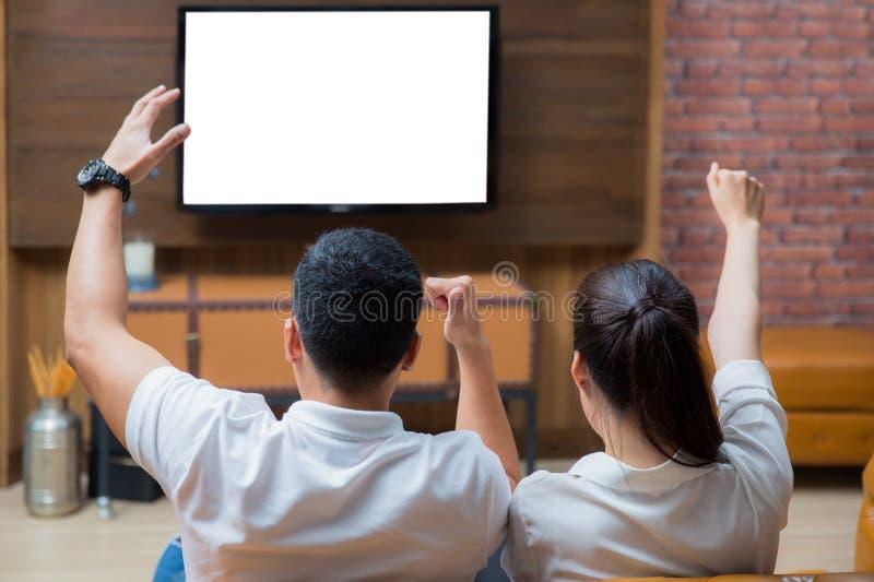 Dois pares asiáticos consideram a televisão no sofá imagens de stock