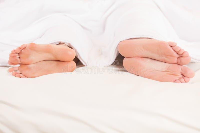 Dois pares de pés longe de se na cama foto de stock royalty free